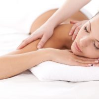 25052571 - total relaxation. beautiful young woman lying on front and looking at camera while massage therapist massaging her shoulders