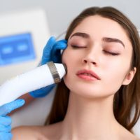 Beautician doctor doing rf-lifting procedure for flawless woman face laying on medical chair in a beauty salon. Hardware cosmetology. Patient receiving electric facial massage. Skin rejuvenation and wrinkle smoothing.