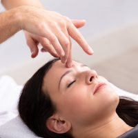 Close-up Of A Young Woman Receiving Reiki Treatment By Therapist 1075627466 בריאות *** Local Caption *** Model Released (MR)
